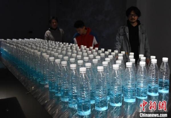 图为由塑料瓶、水和机械装置打造的艺术科技作品吸引市民驻足。 周毅 摄