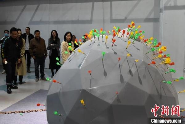 图为展厅内的大型艺术装置吸引参观者围观。 周毅 摄