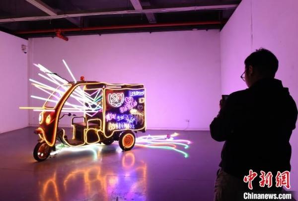 图为用三轮车、霓虹灯等物件打造的艺术作品吸引参观者驻足。 周毅 摄
